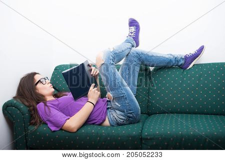 Attractive Girl Reading Storybook On Couch At Home