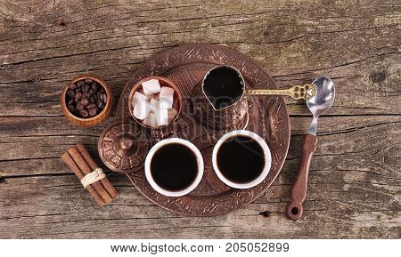 Coffee in copper coasters with accessories for coffee-drinking on old wooden background