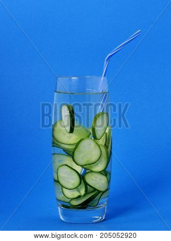 Refreshing and healthy drink of a cucumber in a glass on a blue background