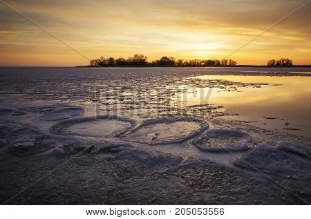 Beautiful Winter landscape with frozen river reeds and sunset sky. Composition of nature.