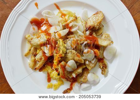 fried chicken with egg topping slice shallot and dressing chili sauce on plate