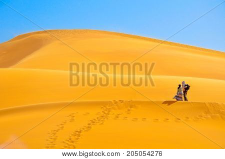 couple walks on high sandy dunes in bright sunny day leave behind marks on sand wind develops the girl's dress