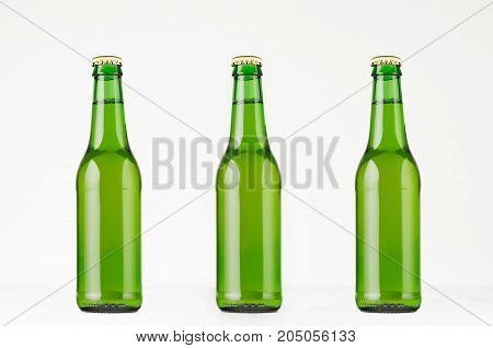 Three green longneck beer bottles 330ml mock up. Template for advertising design branding identity on white wood table.