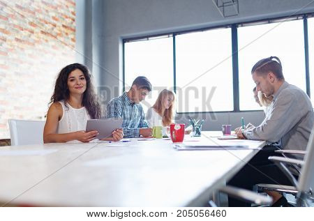 Beautiful woman sitting with colleagues on a meeting on the office background. Business presentation and collaboration. Copy space.
