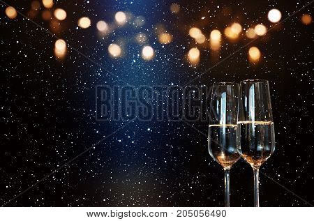 Champagne with blue spotlight and golden bokeh for a new year presentation