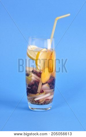 Glass with drink detox dry grapes pear lemon on blue background A refreshing and healthy drink