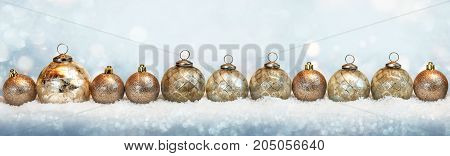Golden christmas balls in the snow with tender bokeh