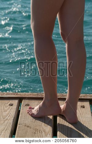 Beautiful female feet stand on a wooden pier.