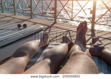 Male and female legs lie on a lounger on the pier at sunset.