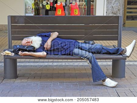 Old Man Is Sleeping On A Bench Outdoor In Sofia, Bulgaria