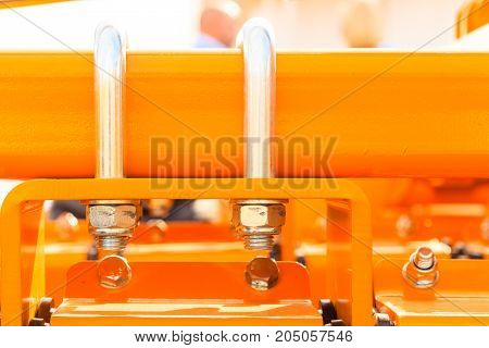 Construction machines concept. Detailed closeup of screws and bolts on yellow indrustrial machinery