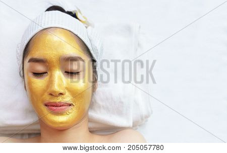 Beautiful young Asian woman relaxing lying on massage table and having high quality and authentic pure gold facial mask for spa treatment to keep her skin glowing hydrated and radiant