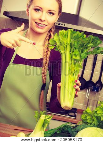 Woman In Kitchen Holds Green Celery