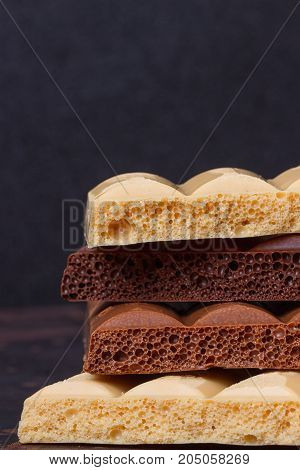 stack of different kind porous chocolate pieces on a dark background.