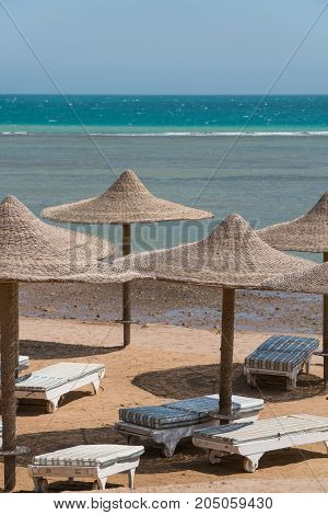 A view of the red sea in Egypt with wicker peaks from umbrellas in the foreground.