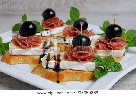 Snack from a toasted slice of baguette with soft under a noble white mold Cheese Brie salami a berry of grapes with honey