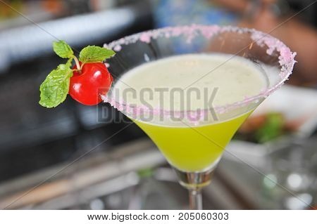 Lime cocktail and red cherry in bar