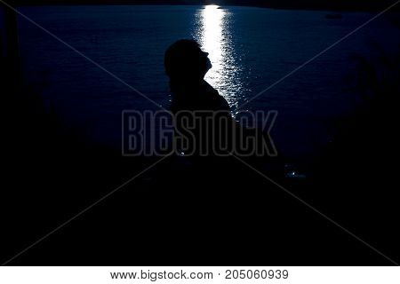 Silhouette of woman in moonlight. They are reflected from the lake.