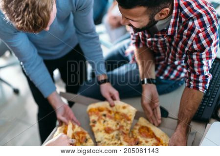Software enginneers sharing pizza on break from work in their company