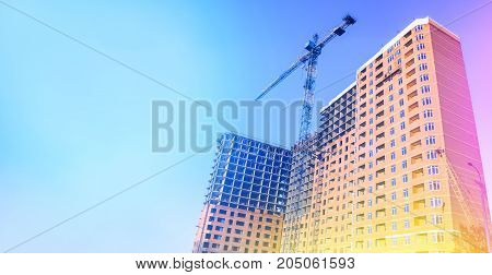 Multi-storey building under construction. Building. Unfinished house. Lifting crane. The concept of development. Toned photo.