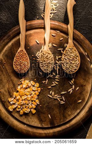 Top view of corn, millet, barley and oat grains in wooden spoons on round wooden tary
