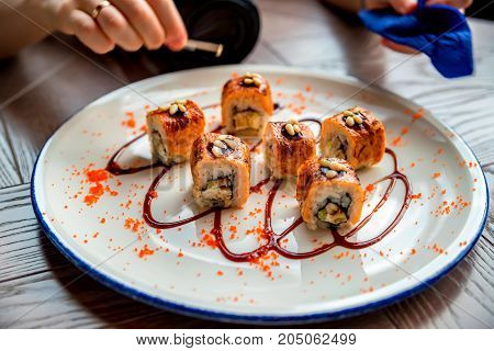 Closeup image of female hands putting pine nuts on top of freshly cooked sushi rolls