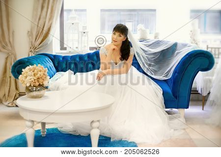 Bride with long veil sitting on a blue sofa