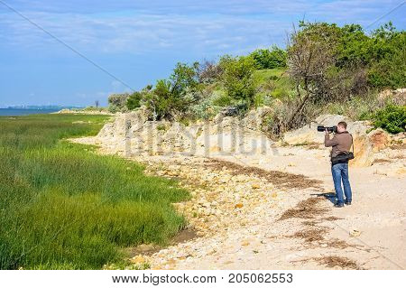 Back view of professional photographer taking pictures of nature on sunny day
