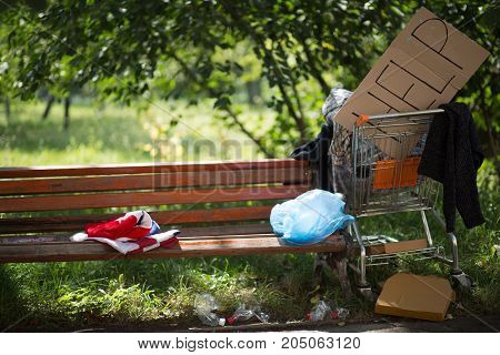 Place of residence of homeless man. Belongings of homeless man on the bench in the park.