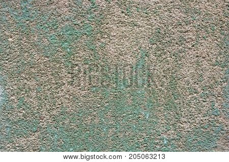 Closeup uneven rough grey plaster texture with old green paint background