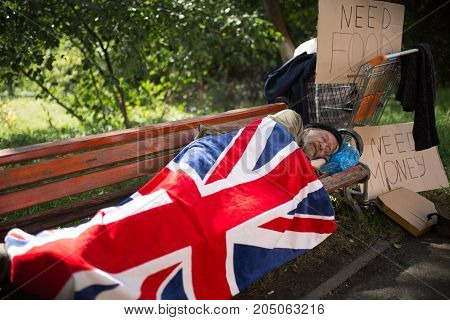 Homeless man sleeping on bench, covering with flag of Great Britain. Poverty, man with no shelter, living in the street.