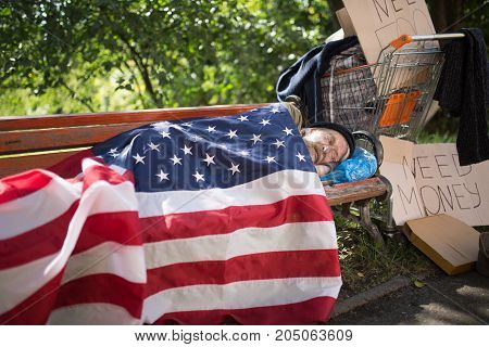 Homeless man using USA flag as a blanket. Old man with no money and home living in the streets.