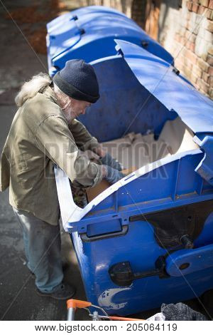 Top view of old homeless male digging in thrash can. Tramp searching for food and empty bottles. poster