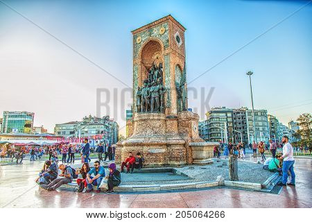 ISTANBUL TURKEY - APRIL 28 2017: People sitting around Republic Monument at Taksim Square in Istanbul. The monument honoring the leaders of the struggle for independence was unveiled in 1928