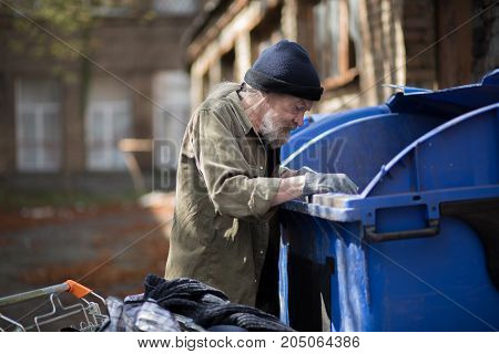 Beardy homeless man searching for empty bottles in trash can. Living in streets concept, male rummaging in garbage.