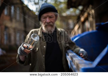 Dirty old tramp looking at empty bottle in his hand. Difficult life of homeless old man.
