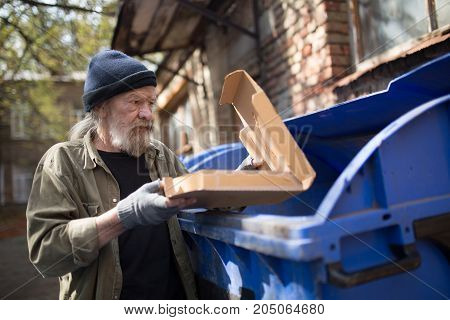 Homeless man standing close to trash can, holding packing from pizza. Tramp looking for food in garbage can.