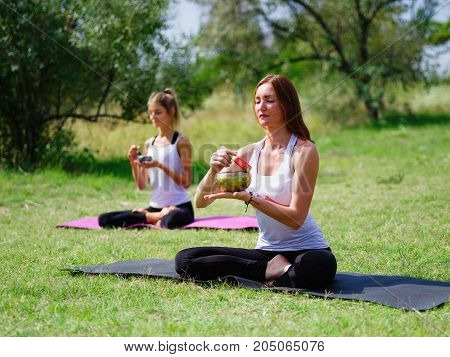 Teacher teaches the meditation of his students in yoga in a summer park. Sport, yoga, assanas concept.
