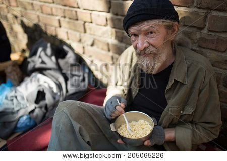 Man with no home, sitting by the brick wall. Homeless man with metal bowl with meal.
