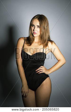 Beautiful oversized model posing in a studio in black body