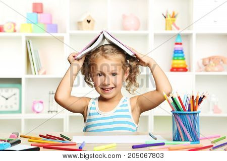 Little girl sitting with book at the table