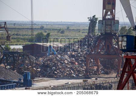 Industrial landscape, mountains of scrap metal, cranes
