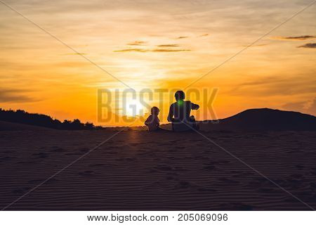 Father and son at the red desert at dawn. Traveling with children concept.
