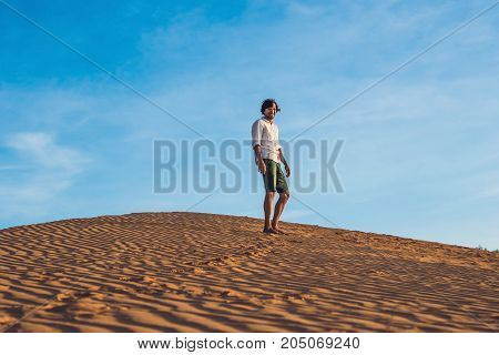 Beautiful young man jumping barefoot on sand in desert enjoying nature and the sun. Fun joy and freedom.