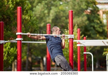 Young strong man train his muscles on training outside. Active life and sport concept.