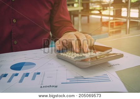 hand working calculate finance about cost with business strategy diagram report calculator on desk at home office income and expenses finance plan money cost savings business economy concept