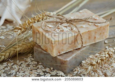 Natural handmade soap oat flakes and wheat ears on wooden background. Spa concept.