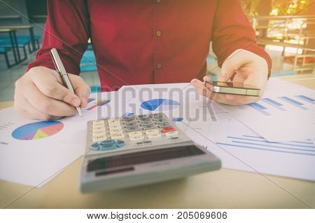 hand working writing and using smart phone with business strategy diagram report calculator on desk at home office income and expenses finance searching data money cost savings economy concept