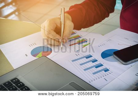 hand writing and working about cost with business strategy diagram report laptop computer and smart phone on desk at home office income and expenses finance money cost savings and economy concept