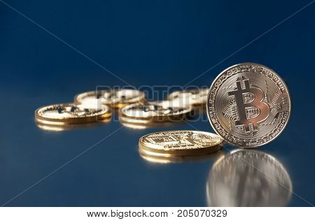 A few gold coins bitcoin lie on a blue background. The concept of crypto currency